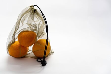 Zero waste, no plastic recycled textile handmade bag with drawstring is used for carrying grocery, fruit, vegetables and greens. Mesh bag is on white background. 写真素材