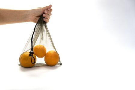 zero wast, no plastic recycled textile handmade bag with drawstring is used for carrying grocery, fruit, vegetables and greens. Woman hang a mesh bag with orange in her hand on white background. 写真素材