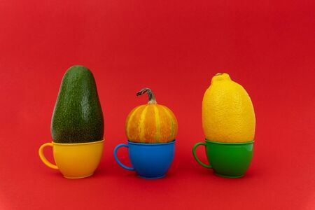 Avocado, pumpkin, lemon in colorful small mugs on red background. Enough space for text. Imagens
