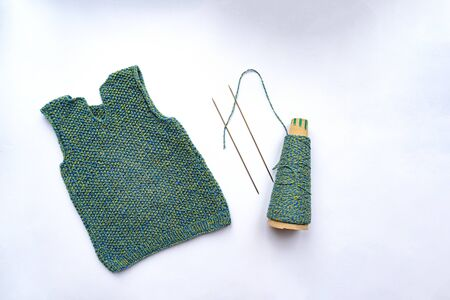 Waistcoat, thread, needles are on white background, view from the top. Knitting concept.