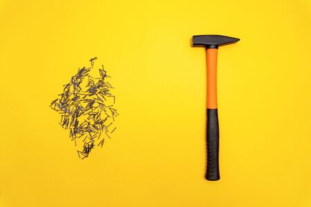 Hammer with orange handle and a pile of stainless nails are on yellow background, minimal housework concept, copyspace