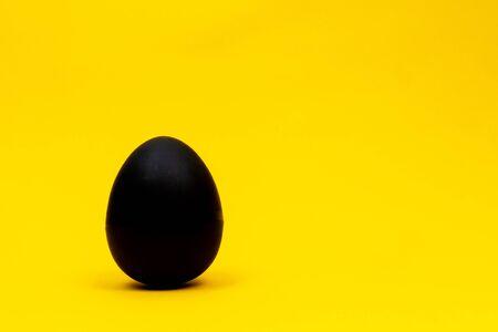 Black egg on yellow background, minimal concept. copyspace.