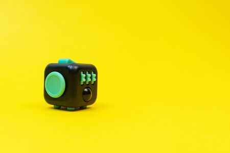 Black and green fidget cube on yellow background, minimal concept, copyspace.