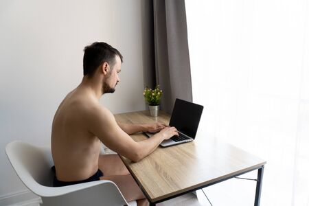 Man in pants should work from home during quarantine time because of coronavirus epidemia. He is freelancer. White background, ilosation concept.