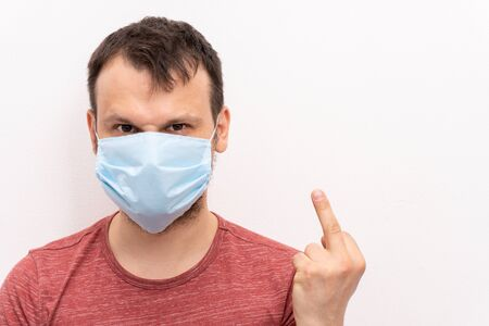 Portraint of caucasian man in facial surgical medical protective mask shows middle fingers as a fucking gesture to coronavirus, close up, end of quarantine is soon. Фото со стока