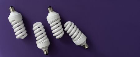 Closeup of white halogen spiral fluorescent light bulb on violet background, saving energy and eco concept, top view, banner, space for text.