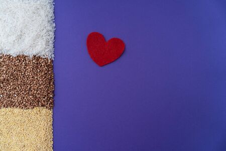 Purple background with brown fried buchwheat, yellow millet and red heart symbol, donation concept during quarantine, cereal concept, copy space,