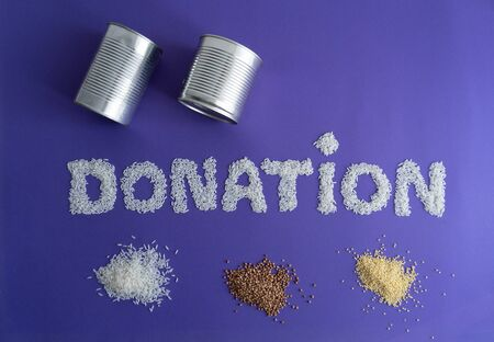 Closeup of word donation made from white rice and small piles of rice, buckwheat and millet under the word donation. Two cans above the word donation. Minimal supporting concept. purple background