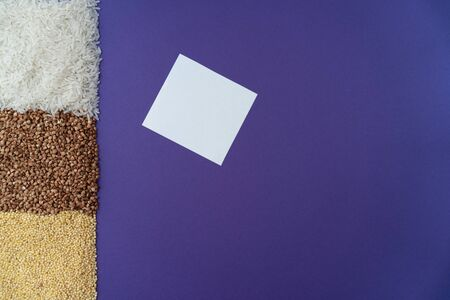 Purple background with white rice, brown fried buchwheat, yellow millet and white paper blank note, donation concept during quarantine, cereal concept, copy space, Stockfoto