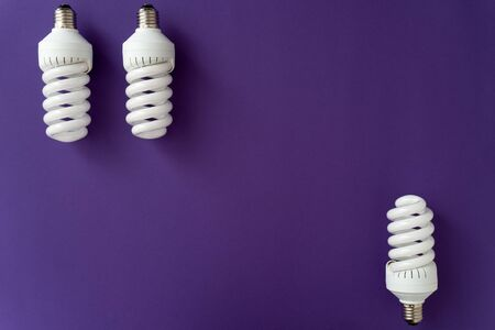 Two halogen white lamps on the top of violet background and one halogen lamp on the bottom, copy space in center, no people, flat lay.