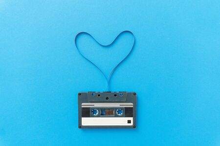 Closeup of retro audio stereo mono black cassete with magnetic tape in shape of heart. Top view at the cassete on blue backgrpund, copyspace. Stock fotó - 149384674