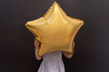 Closeup of caucasian child hanging gold star balloon with hands and hidding face, black background, copy space, celebration concept.