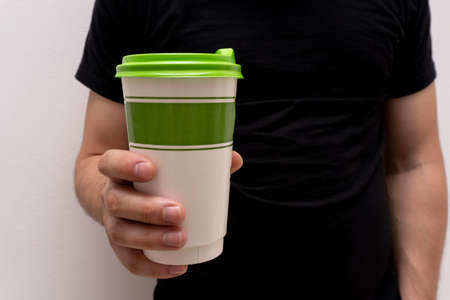 Closeup at takeaway paper eco green coffee cup with green cover at mans hand, mockup and copy space. Standard-Bild