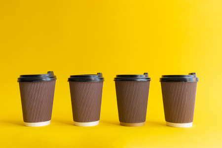 Four brown togo coffee paper cups with black covers on yellow background, one cup differs from others. copy space. 版權商用圖片