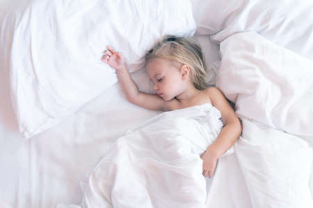 Cute caucasian kid wakes up after sleeping on bed with white linen, raising hands, top view, good background, copy space, toned, early morning.