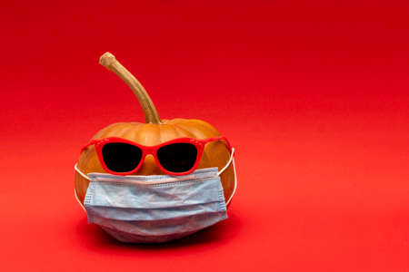 Pumpkin with red sunglasses and face protective medical mask, autumn concept in modern world with coronavirus, red background, copyspace.. Imagens