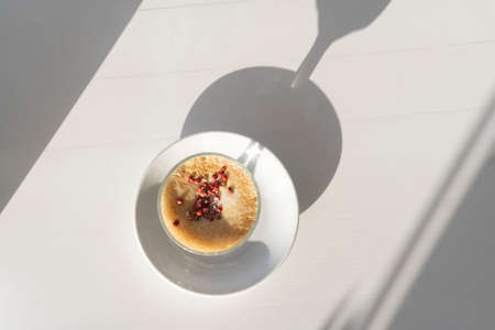 Aromatic tasty coffee drink at ceramic cup with shadows on white table background, copy space, top view, inspiration morning concept.