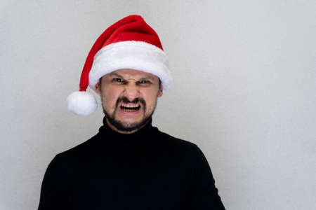 Young caucasian man at red Santa hat is crying and angry, grey background, copy space.