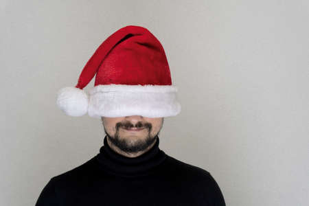 Caucasian bearded man at red Santa cap with hidden eyes copy space, Christmas and new year concept. Stockfoto
