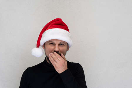 Caucasian man at red Santa hat coughing, grey background, copy space