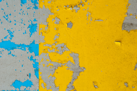 fragment of an iron surface is covered with blue and yellow color paint, which has long been under the influence of different climatic conditions