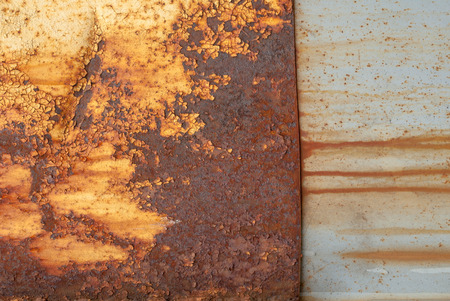 influenced: rusty iron surface covered with old chipped yellow color paint, which has long been influenced by different climatic conditions