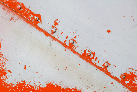 fragment of an iron surface is covered with orange and grey color paint, which has long been under the influence of different climatic conditions