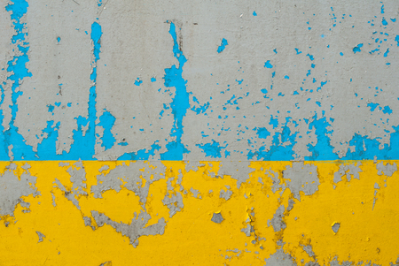corrosion: fragment of an iron surface is covered with blue and yellow color paint, which has long been under the influence of different climatic conditions