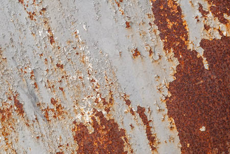 rusty iron surface covered with old chipped grey color paint, which has long been influenced by different climatic conditions