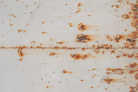 rusts: fragment of an iron surface is covered with grey color paint, which has long been under the influence of different climatic conditions