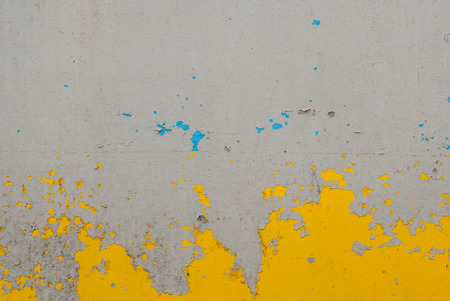 fragment of an iron surface is covered with grey and yellow color paint, which has long been under the influence of different climatic conditions Stock Photo