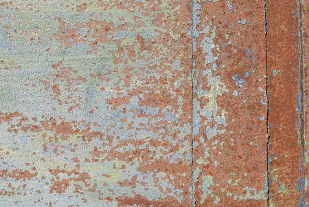 fragment of a rusty iron surface covered with old paint, which has long been under the influence of different climatic conditions