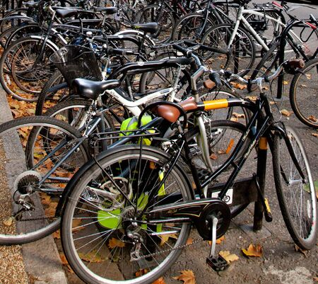 close up of many bicycles chained up at on road bike parking