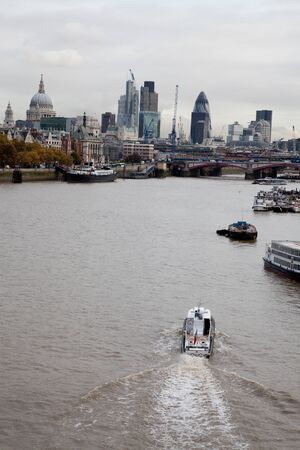 the River Thames looking east towards St.Pauls cathedral and the city with a boat in the foreground , portrait format