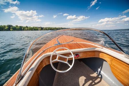 fibra de vidrio: Vista de ángulo amplio de un barco de deporte clásico de madera en un día soleado.