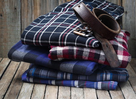 neatly stacked: Mens clothes, neatly stacked on wooden background Stock Photo