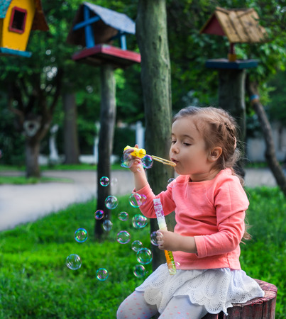 feeders: little girl with soap bubbles in a Park near the feeders Stock Photo