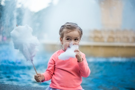 the emotions of a little girl with cotton candy near the fountain