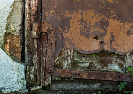 godforsaken: old door and rusty hinges in the village