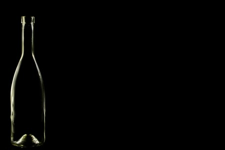 in low spirits: glass bottle, empty, original, on black background space for text