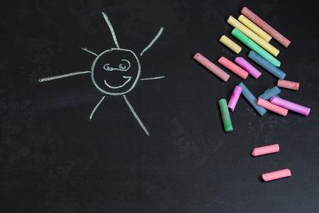 Gessi colorati su una lavagna nera con disegni del sole