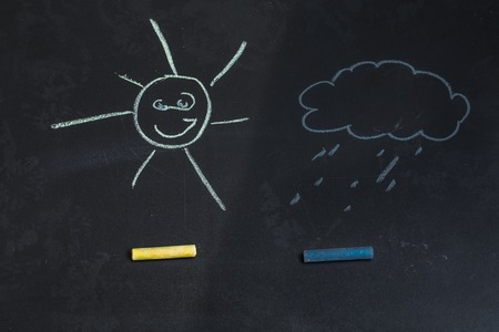 chalks: colored chalks on a black blackboard with drawings of a sun and a cloud Stock Photo