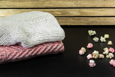 rack arrangement: neatly folded sweaters on a wooden background with decoration