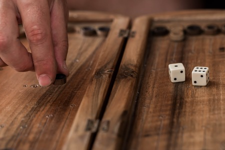 gambling stone: wooden Board with backgammon, pawns with dice, close up