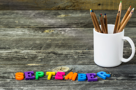 school supplies on wooden background, Notepad, pencils with the word September Zdjęcie Seryjne