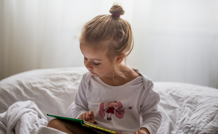 a little girl reads a children's book in bed after sleep Banque d'images