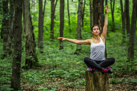 sportwoman: Warming-up. Beautiful sporty girl in the woods on a stump in yoga, sports