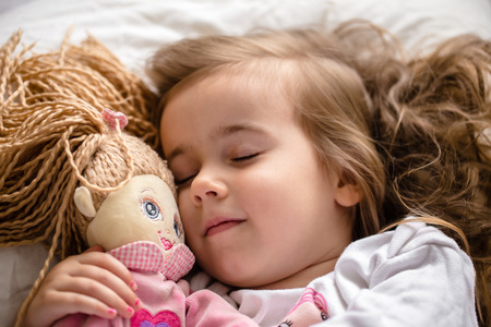 a little girl falls asleep in bed with soft doll, white bed