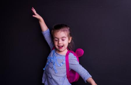 Petite belle fille sur un fond noir, avec une serviette sur ses épaules montrant différentes émotions