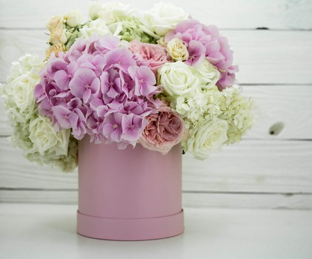 beautiful fresh flowers peonies in the pink box with fruits on wooden white background